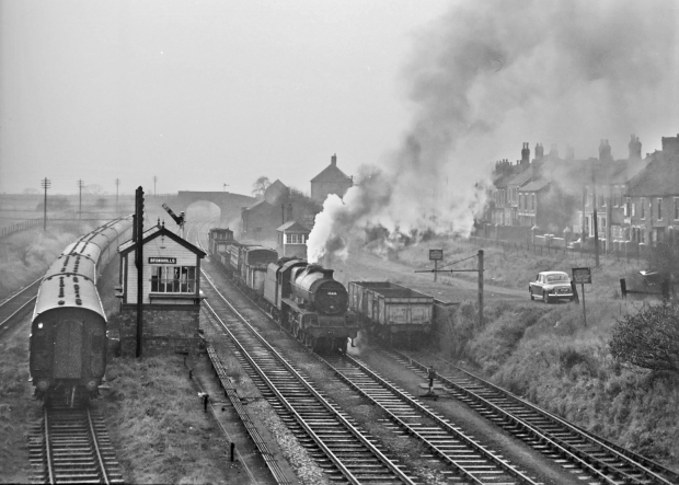 It was a dull and damp 2nd December in 1962 when Peter paid a visit to Brownhills in Staffordshire. He was in time to see Jubilee 45626 Seychelles, at the time a Burton based engine, working a mixed freight. The loco is blowing steam from her safety valve which would suggest it has been stopped. 45626 lasted until November 1965 a life of 31 years. The sidings to the left are being used to stable coaching stock but a short raft of wagons occupy the goods yard. The road down to the yard has a fine Rover 80 parked in it, as it is opposite to the signal box maybe it is the signalman's Pride and Joy.