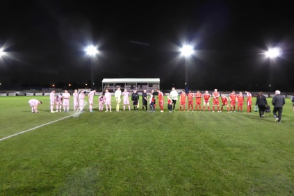 Customary pre-match handshake . The Wood wore red shirts and shorts. Highgate had bright pink tops and bottoms.