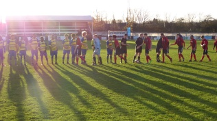 Late November low level sun and a bitingly cold afternoon as Pelsall, in red and Moors shake hands before the start of a captivating game of soccer.